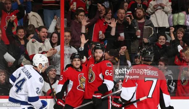 Clarke MacArthur of the Ottawa Senators celebrates his first period goal shorthanded goal with teammates Eric Gryba and Kyle Turris as Ryan Callahan...