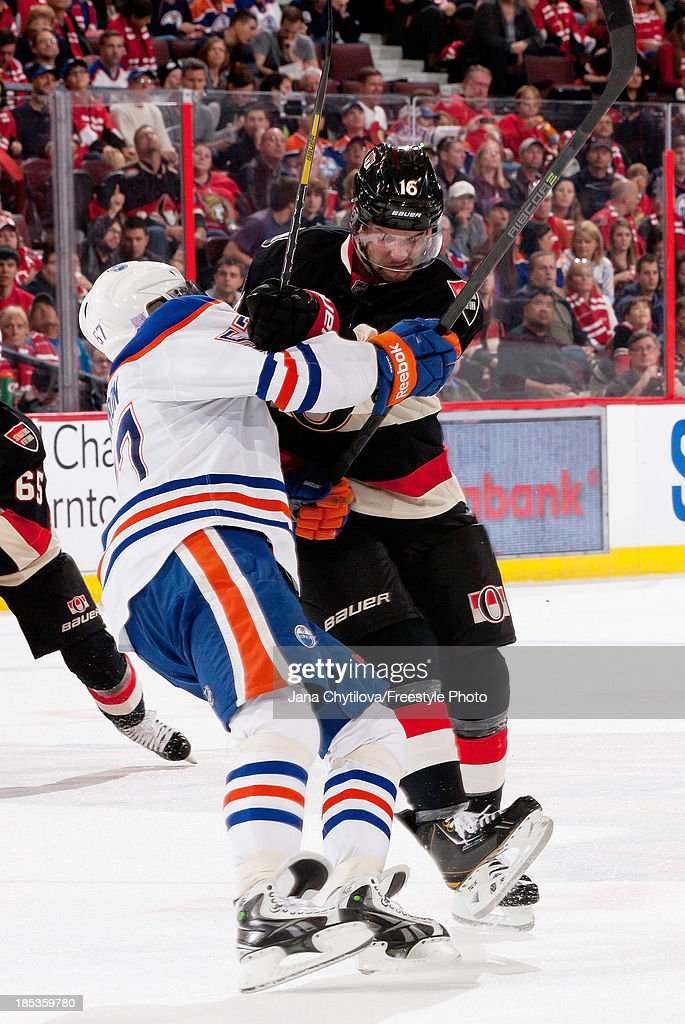 <a gi-track='captionPersonalityLinkClicked' href=/galleries/search?phrase=Clarke+MacArthur&family=editorial&specificpeople=3949382 ng-click='$event.stopPropagation()'>Clarke MacArthur</a> #16 of the Ottawa Senators checks <a gi-track='captionPersonalityLinkClicked' href=/galleries/search?phrase=David+Perron&family=editorial&specificpeople=4282591 ng-click='$event.stopPropagation()'>David Perron</a> #57 of the Edmonton Oilers during an NHL game at Canadian Tire Centre on October 19, 2012 in Ottawa, Ontario, Canada.