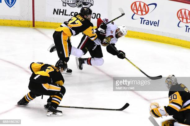 Clarke MacArthur of the Ottawa Senators falls to the ice against Carter Rowney of the Pittsburgh Penguins during the third period in Game Seven of...