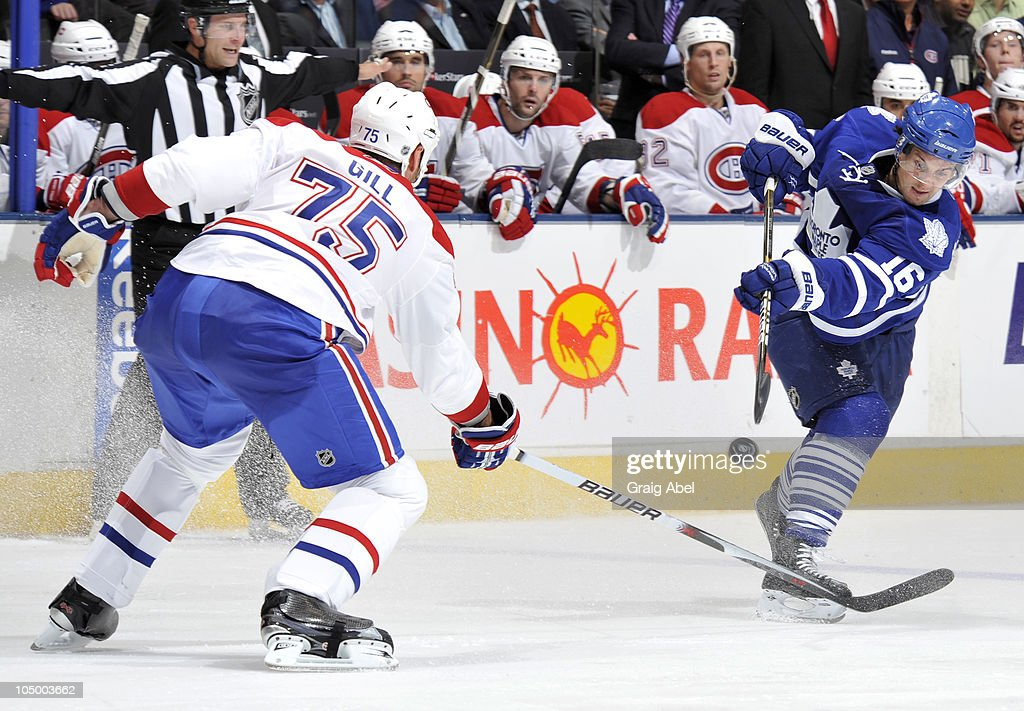 <a gi-track='captionPersonalityLinkClicked' href=/galleries/search?phrase=Clarke+MacArthur&family=editorial&specificpeople=3949382 ng-click='$event.stopPropagation()'>Clarke MacArthur</a> #16 of the Toronto Maple Leafs shoots the puck past <a gi-track='captionPersonalityLinkClicked' href=/galleries/search?phrase=Hal+Gill&family=editorial&specificpeople=209158 ng-click='$event.stopPropagation()'>Hal Gill</a> #75 of the Montreal Canadiens during game action October 7, 2010 at the Air Canada Centre in Toronto, Ontario, Canada.