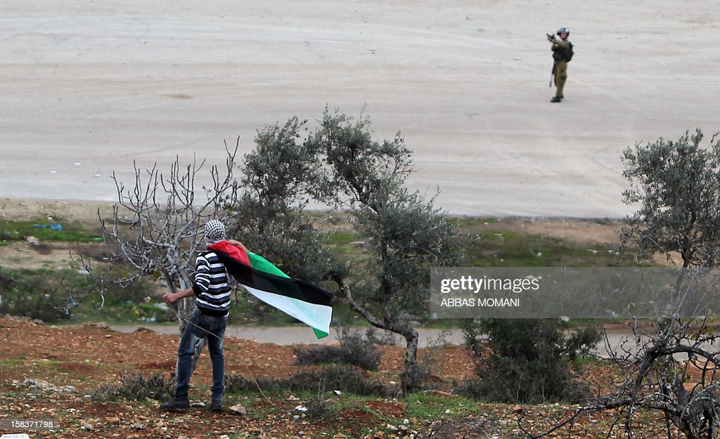 Clashes between Palestinian youth and Israeli soldiers near Ofer military prison, near the West Bank city of Ramallah, as protestors gathered following the 25th anniversary of the founding of Hamas on December 14, 2012. AFP PHOTO / ABBAS MOMANI