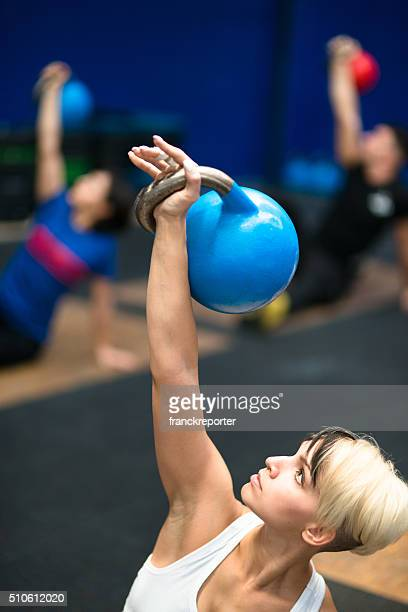 class lifting a kettlebells in a gym