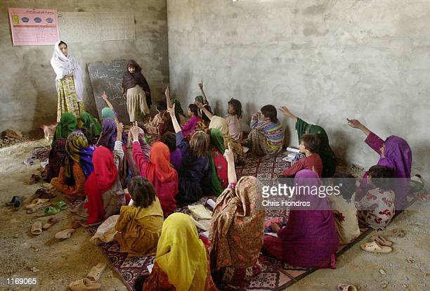 A class of Afghan refugee girls raise their hands October 18 2001 at the Shamshatu Afghan refugee camp in Pakistan near the border of Afghanistan...