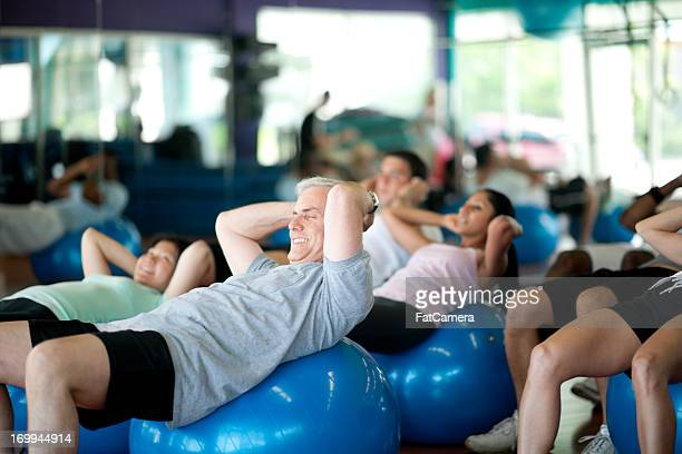 Class on exercise balls working out in gym