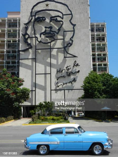 A classic American car drives by an image of Che Guevara whose face adorns the Ministry of Interior building in Revolution Square