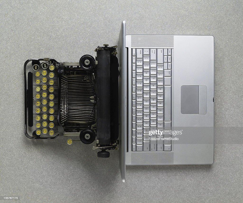 Classic analog typewriter vs Modern digital hi-tech laptop computer : Stock Photo