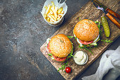 Two tasty grilled classic beef burgers with French fries on a rustic black table, top view with copy space