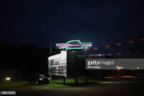 A classic car illuminated with neon at night sits on top of the feature presentations billboard at the Georgetown DriveIn movie theater in Georgetown...