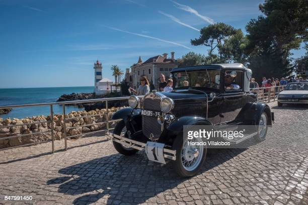 A classic car si being driven on Rei Humberto II de Italia Avenue in front of Santa Marta Lighthouse during Cascais Classic Motor Show on September...