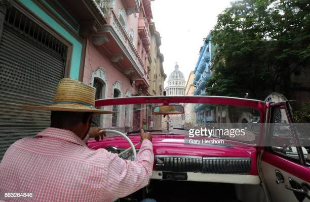 A classic car taxi driver makes his way to the Capitolio on October 8 2017 in Havana Cuba