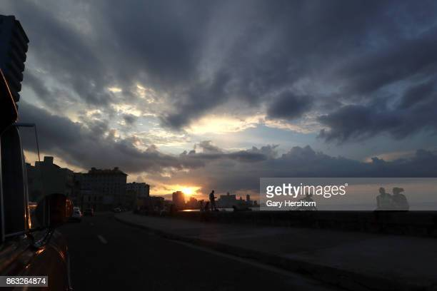 A classic car taxi drives along the Malecon as sunset on October 8 2017 in Havana Cuba