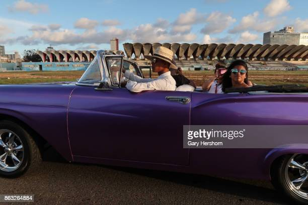 A classic car taxi drives along the Malecon at sunset on October 9 2017 in Havana Cuba