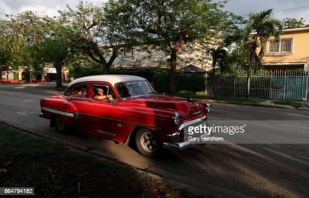 A classic car taxi drives drives through the neighbourhood of Miramar on October 13 2017 in Havana Cuba