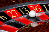 Classic casino roulette wheel with black sector thirteen 13 and white ball and sectors 6, 27, 36, 11