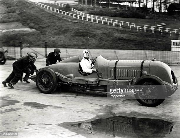 Classic Collection Page 106 1930 Driver in supercharged Bentley motor car being pushed onto track by two men at Brooklands race track Surrey England
