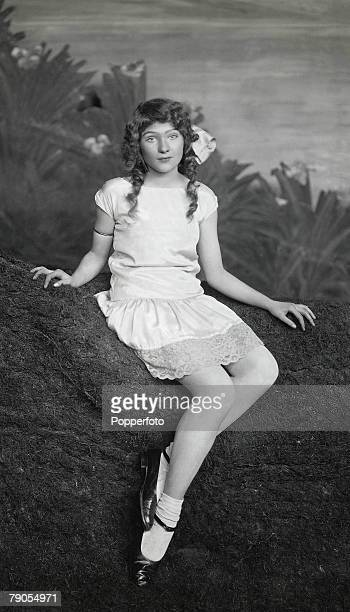 Classic Collection Page 134 Young woman with ringlets and a ribbon in her hair sitting on a stage set consisting of mock grass and painted scenery...