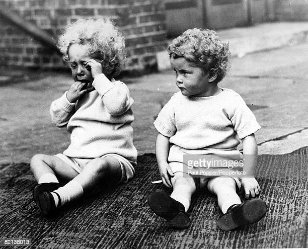 Classic Collection Page 27 15th November 1931 Two curly haired children sit on a rug outdoors one bursting into tears