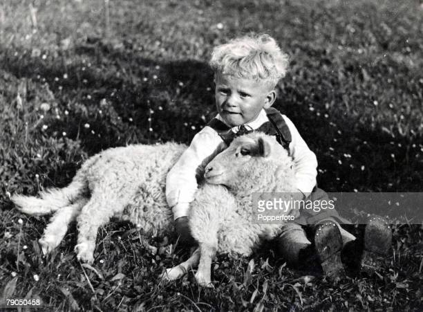 29 Maine USA A young boy with blonde curly hair cuddling a sheep in Canada