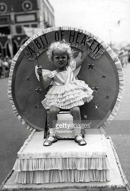 30 NewJersey USA A young blonde curly haired girl sitting on a float and waving a wand wearing a frilly dress at a baby contest in Absury Park New...