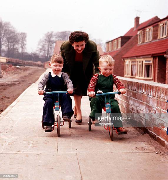 Classic Collection Page 30 Two small boys being pushed on tricycles by a woman towards the camera