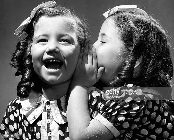 Classic Collection Page 31 Two girls with ringlets in their hair wearing spotted dresses One girl is whispering in the others ear