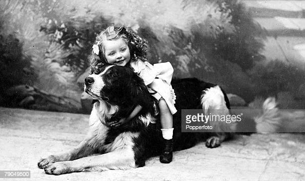 Classic Collection Page 32 Studio portrait of a young girl with ringlets sitting on and cuddling a large dog