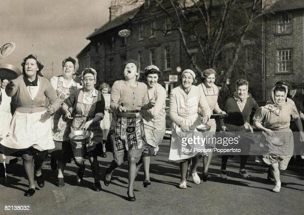 Classic Collection Page 73 Group of women wearing aprons running and tossing pancakes as they race down the street Britain Buckinghamshire Olney