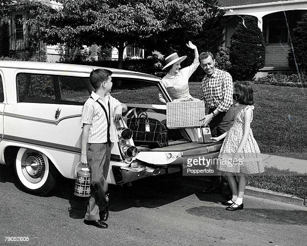 Classic Collection Page 88 Young family packing a picnic basket and flask into a car Woman wearing hat is waving