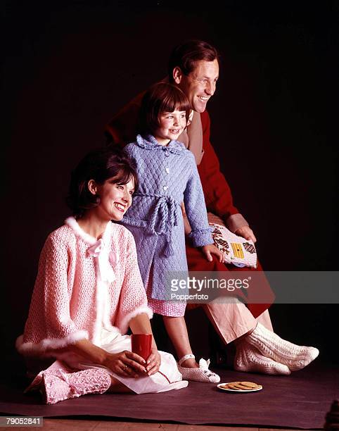 Classic Collection Page 89 Young family group in knitwear fashion pose Woman wearing pink bed jacket with fur trim girl wearing blue dressing gown...