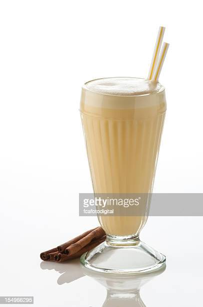 Classic glass of vanilla milkshake on white backdrop.