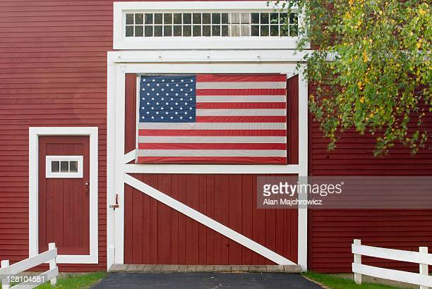 Classic New England farm with red barn and white fence. American flag on barn door. Vermont. USA
