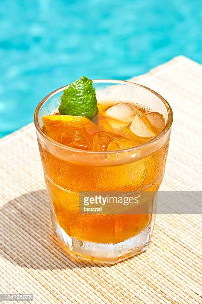 Classic Old Fashioned cocktail near waterpool on the mat