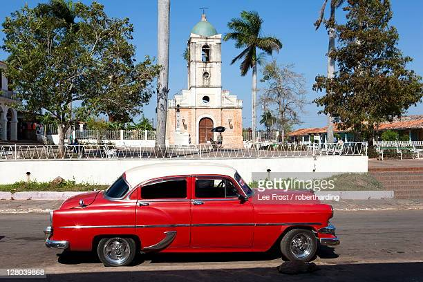 Classic red American car parked by the old square in Vinales village, Pinar del Rio, Cuba, West Indies, Central America