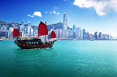 The Hong Kong skyline from the harbor at daytime.  The water is blue-green, and a traditional Chinese junk ship with square red sails is in the water in the foreground.  The buildings in the skyline a