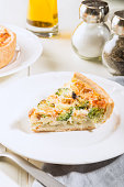 Classic salmon and broccoli quiche made from shortcrust pastry with broccoli florets and smoked salmon in a creamy free range egg custard