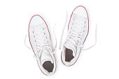 Classic white sneakers with untied the laces isolated on white background top view