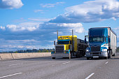 Two semi trucks of various models and manufacturers, a yellow classic American semi truck with a bulk trailer and a blue modern American semi truck with a high trailer for bulk cargo rushing along a w