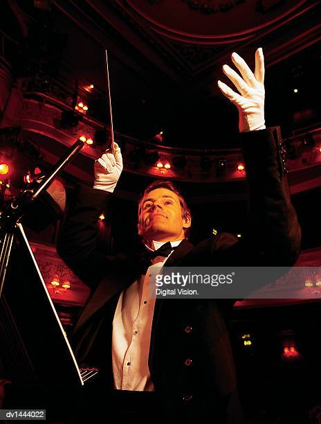 Classical Music Conductor Raising His Arms in an Auditorium