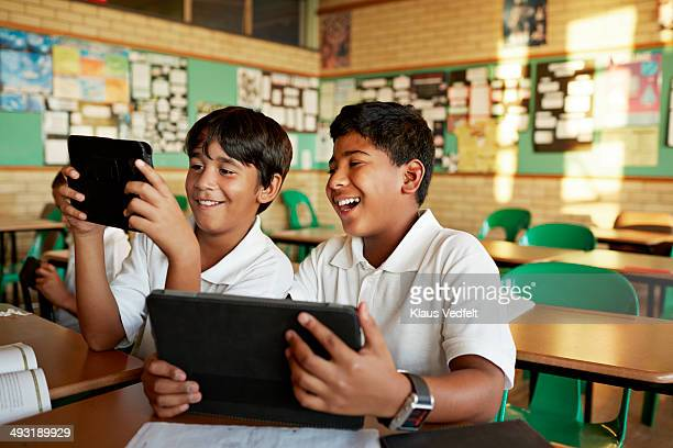 Classmates looking at tablets together