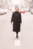 classy business woman standing on a city road
