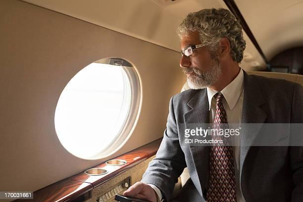 Élégant Homme d'affaires avec téléphone mobile sur un jet privé