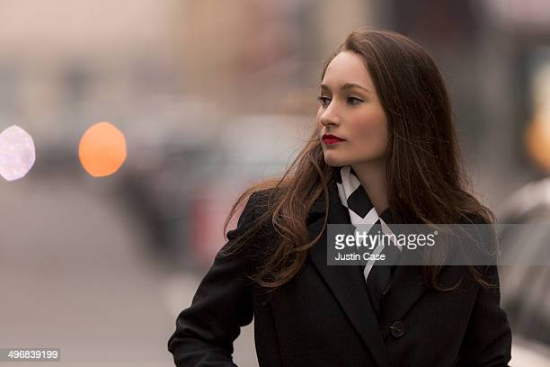 classy urban woman staring away in the city