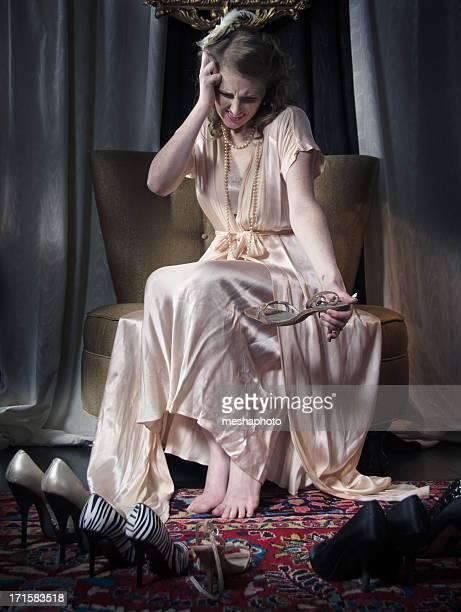 Stilvolle Frau mit einem Kopfschmerz über Auswahl Schuhe