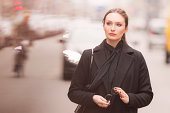 classy woman holding glasses among the blurry city