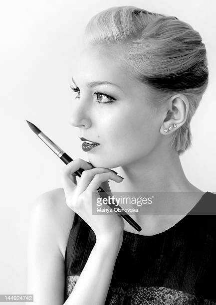Classy woman looking thoughful with paintbrush