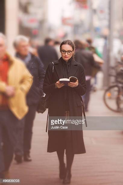 classy woman walking and reading in the street