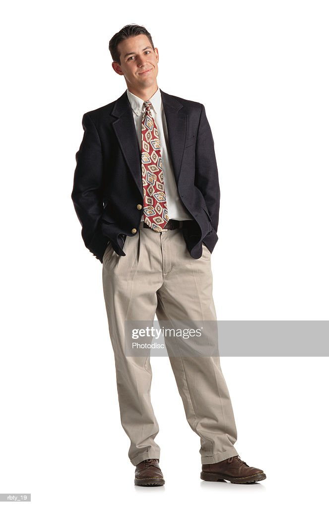 classy young buisness man in a suit with tie and khaki pants and navy blazer standing with weight shifted and a smirk on his face : Stock Photo