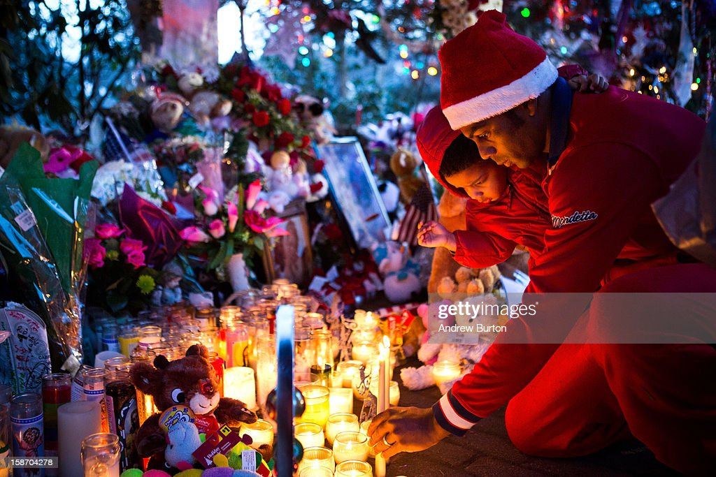 Claud Oliveira holds his son, Jeremiah Oliveira, while lighting a candle at a memorial for those killed in the school shooting at Sandy Hook Elementary School on December 24, 2012 in Newtown, Connecticut. Donations and letters are pouring in from across the country as the town tries to recover from the massacre.