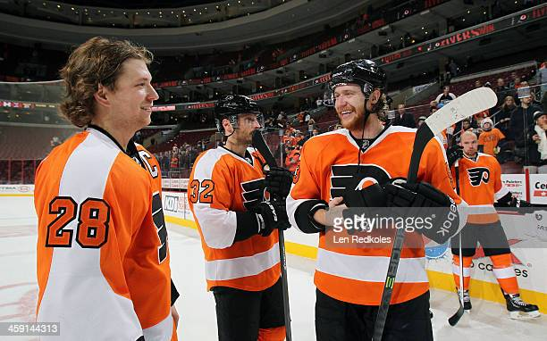 Claude Giroux and Mark Streit and Jakub Voracek of the Philadelphia Flyers gather prior to the father and son team photo following their game against...