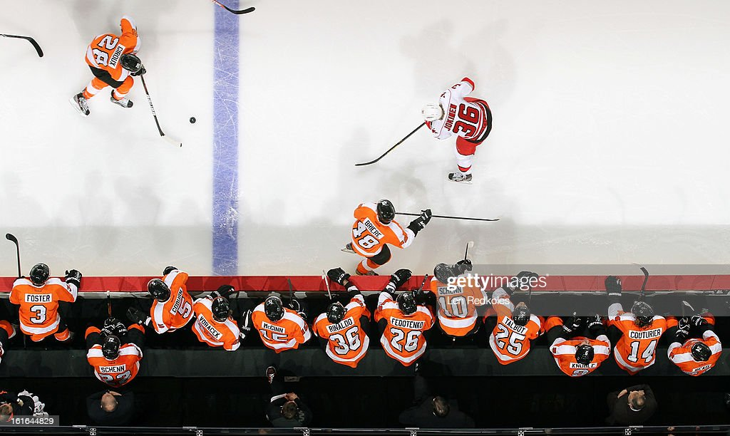Claude Giroux #28 looks to pass the puck to Danny Briere #48 of the Philadelphia Flyers as they skate in front of the bench against Jussi Jokinen #36 of the Carolina Hurricanes on February 9, 2013 at the Wells Fargo Center in Philadelphia, Pennsylvania.